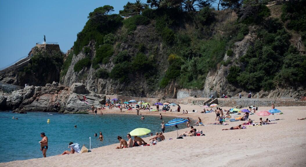 Decenas de personas disfrutan de un día en una playa en medio de la reapertura al turismo en Lloret de Mar, España, el 22 de junio de 2020.