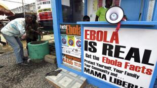 Dos personas se lavan las manos al lado de un puesto de información sobre el ébola, en Monrovia, Liberia, el 30 de septiembre de 2014