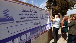Des employés de la Commission électorale du référendum kurde accrochent des bannières aux abords des bureaux de vote à Erbil le 24 septembre 2017.