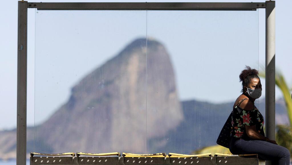 Una mujer espera el bus el 11 de mayo durante la pandemia por el Covid-19, con el morro Pan de Azúcar detrás de ella, en Río de Janeiro, Brasil.