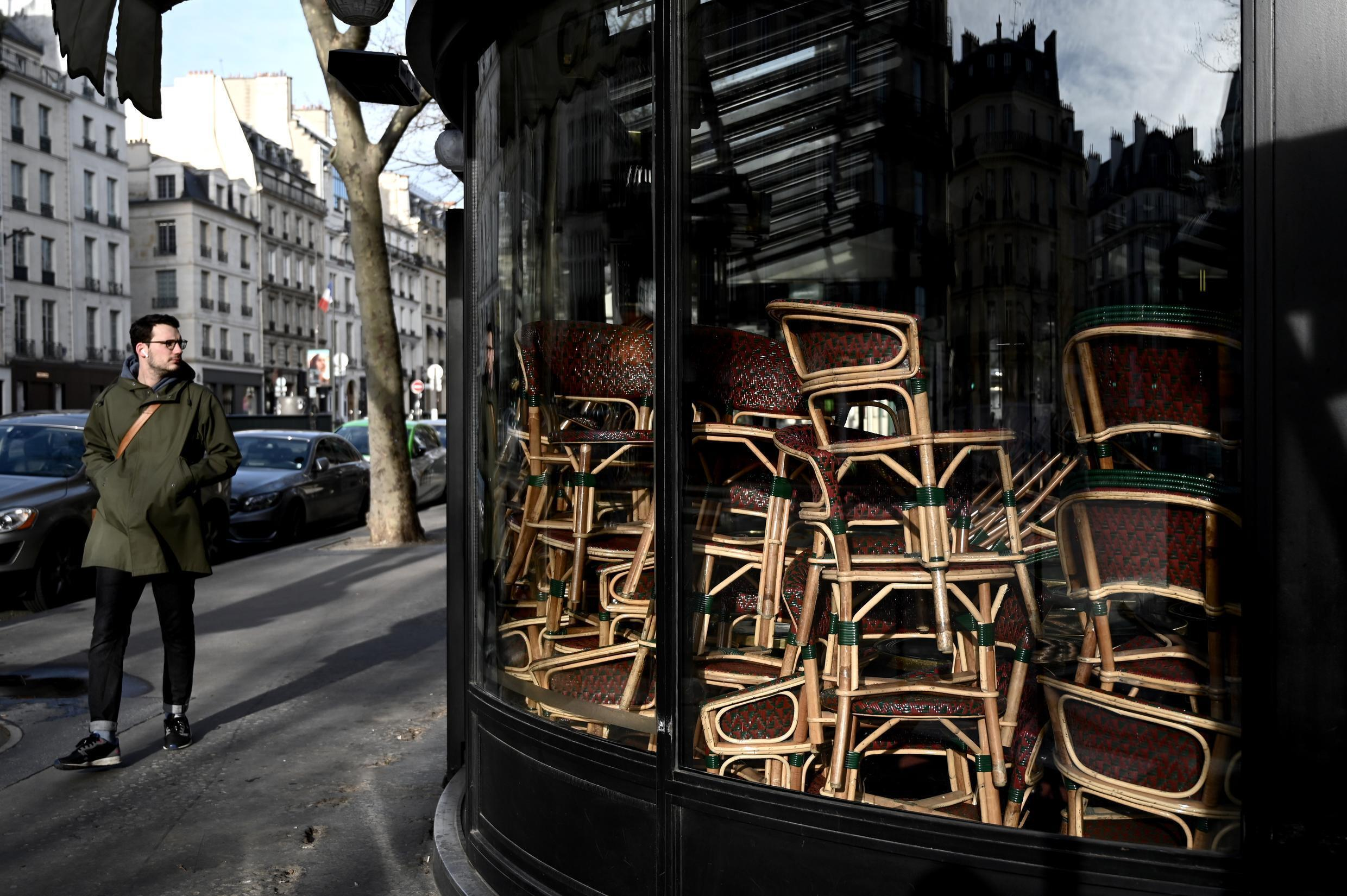 A man walks by the shuttered Café de Flore on Sunday, March 15, 2020, after restaurants were ordered to close as of midnight Saturday.