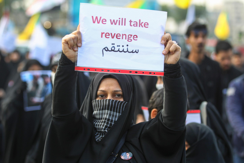 Une Irakienne tient une pancarte appelant à la vengeance contre les États-unis, le 4 janvier 2020 à Bagdad.