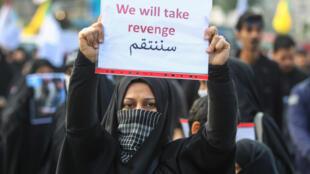 """عراقية ترفع لافتة تدعو للـ""""انتقام"""" من الولايات المتحدة بعد مقتل سليماني، 4 يناير/كانون الثاني 2020 في بغداد"""