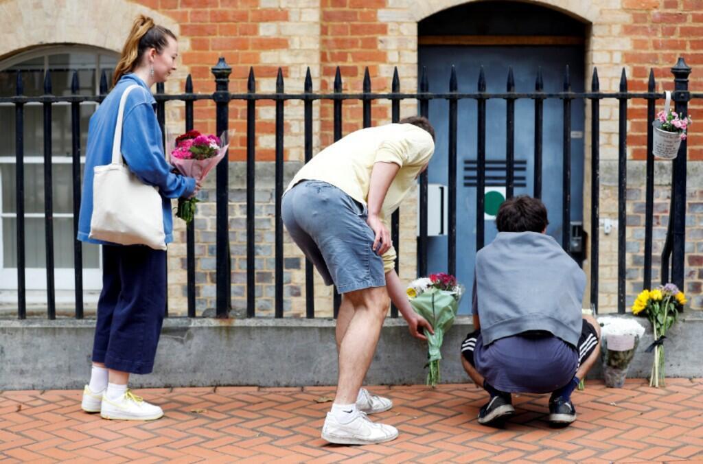 La gente deja flores junto al cordón policial en la escena de múltiples apuñalamientos en Reading , Gran Bretaña, 21 de junio de 2020.