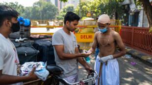 Des bénévoles, dont un habillé comme le héros de l'indépendance indienne, le Mahatma Gandhi, dont c'est l'anniversaire, distribuent des masques aux conducteurs de vélos-taxis, à New Delhi le 2 octobre 2020