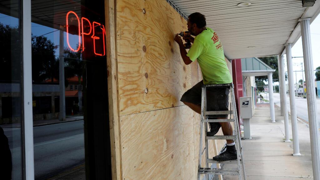 Un hombre se prepara ante la llegada de la huracán a Florida apuntalando la cristalera de su comercio.