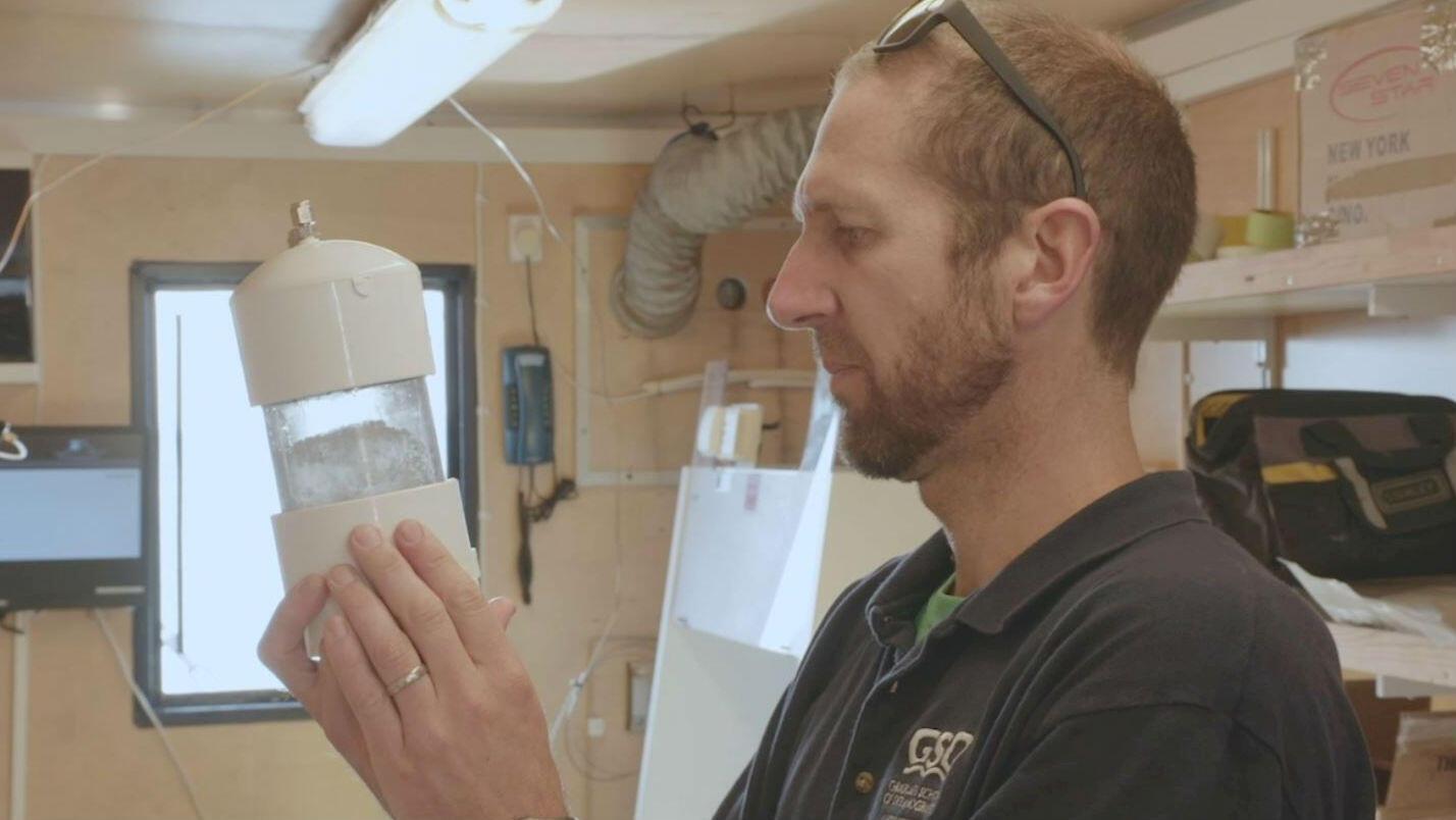 El Dr. Brice Loose, Jefe Científico del Proyecto del Pasaje del Noroeste inspecciona una muestra tomada de un núcleo de hielo en el Ártico canadiense, el 14 de agosto de 2019.