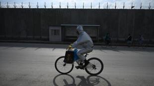 رجل يرتدي الملابس الواقية من كورونا على دراجة هوائية في كابول في 20 نيسان/ابريل 2020.