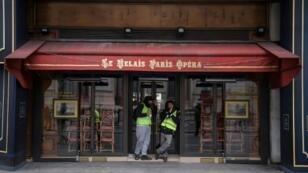 """Deux """"gilets jaunes"""" mangent un sandwich devant un café fermé place de l'Opéra à Paris, le 15 décembre 2018"""