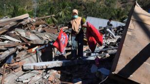 Des habitants fouillent des décombres à la recherche de leurs biens à Menggala, au nord de l'île de Lombok, le 8 août 2018.