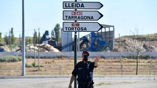 A Catalan regional police officer controls a checkpoint on the road leading to Lleida on July 4, 2020. Spain's northeastern Catalonia region locked down the area following a surge in new coronavirus cases.