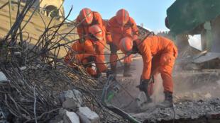Des secouristes tentant de sauver les personnes restées sous les décombres d'une mosquée à Tanjung, dans le nord de Lombok.
