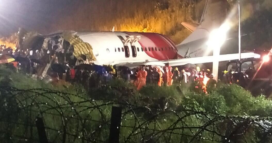 Socorristas rodean los restos de un avión de Air India Express, que transportaba a más de 190 personas desde Dubai, después de que se estrelló al sobrepasar la pista de aterriza del Aeropuerto Internacional de Kozhikode, en Karipur, India, el 7 de agosto de 2020.