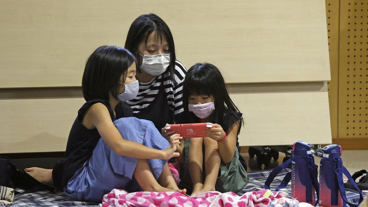 """أسرة يابانية تحتمي من إعصار """"هايشن"""" داخل مركز إجلاء في كاجوشيما، اليابان في 6 سبتمبر/أيلول 2020."""