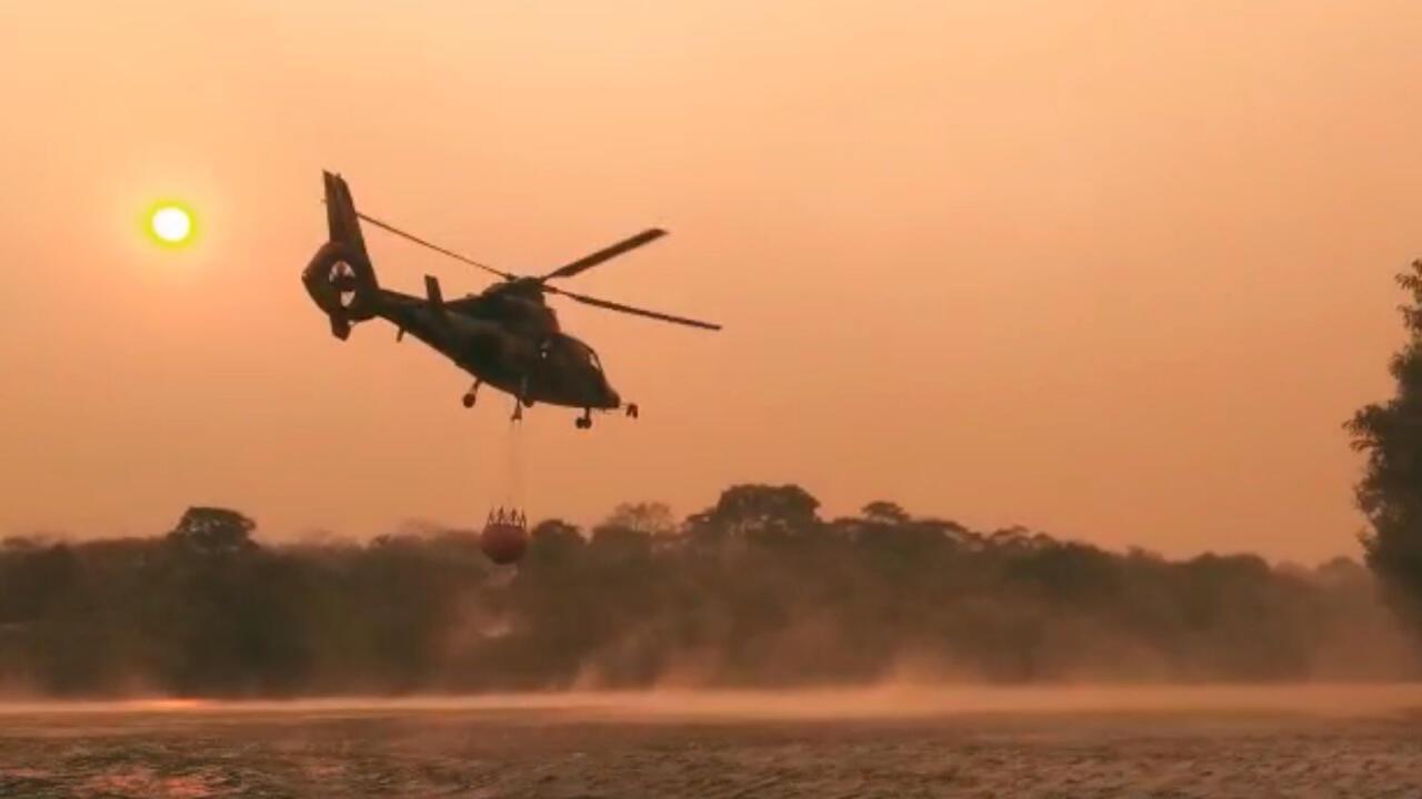 Un helicóptero de la Fuerza Aérea de Bolivia recoge agua para combatir incendios forestales, cerca de Robore, Bolivia , el 19 de agosto de 2019.