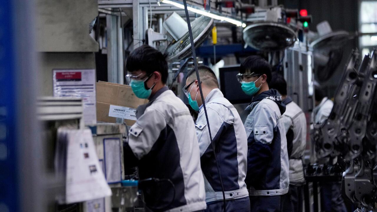 Los empleados que usan máscaras faciales trabajan en una línea de ensamblaje de asientos de automóviles en la fábrica Yanfeng Adient en Shanghai, China, cuando el país se ve afectado por un brote de un nuevo coronavirus, el 24 de febrero de 2020.