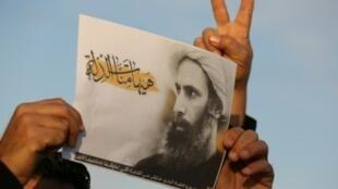 متظاهر يحمل صورة رجل الدين الشيعي نمر النمر