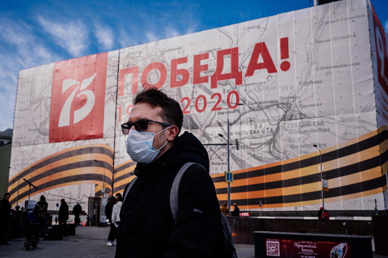 Un hombre con mascarilla pasa junto a una pancarta para la celebración del 75 aniversario del fin de la Segunda Guerra mundial. Moscú, Rusia.