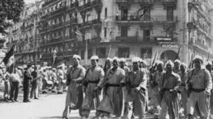 فرقة من الحركيين خلال استعراض عسكري في الجزائر في 8 أيار/مايو 1957 في ذكرى انتهاء الحرب العالمية الثانية