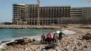 عناصر من الصليب الأحمر يحملون جثث مهاجرين غرقوا قبالة السواحل الليبية 4 يناير 2017