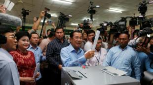 El primer ministro de Camboya y presidente del Partido Popular Camboyano (CPP) Hun Sen se prepara para emitir su voto mientras su esposa Bun Rany permanece a su lado en una mesa electoral durante unas elecciones generales en Takhmao, provincia de Kandal, Camboya el 29 de julio de 2018.