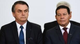 Le président brésilen Jair Bolsonaro (à gauche) aux côtés du vice-président Hamilton Mourao, lors d'une cérémonie marquant les 100 premiers jours du gouvernement, à Brasilia, le 11 avril 2019.