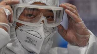 Un miembro de la seguridad del aeropuerto con indumentaria protectora por el coronavirus se ajusta las gafas durante un control de pasajeros llegados al aeropuerto internacional de Shanghái Pudong, el 26 de marzo de 2020 en la ciudad china
