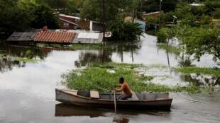 Un hombre rema en una calle inundada por las fuertes lluvias que provocaron el desborde del río Paraguay, en los suburbios de Asunción.