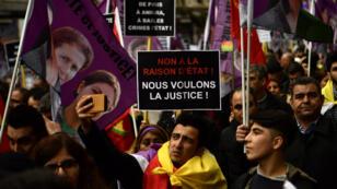 """Un manifestant tient une pancarte """"Nous voulons la justice"""" lors du défilé en hommage aux trois militantes kurdes assassinées à Paris en 2013, le 6 janvier 2017."""