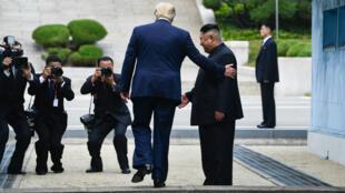Kim Jong-un et Donald Trump sur la ligne de démarcation militaire qui sépare les deux Corées, le 30juin2019.