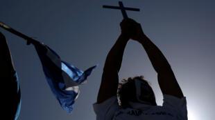 """Un expatriado nicaragüense enseñando una cruz en señal de resistencia durante la """"Caravana por la Libertad y la Justicia"""" que se llevó a cabo en la frontera entre Costa Rica y Nicaragua el 16 de diciembre de 2018."""