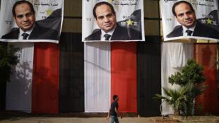 Un Égyptien passe devent un bureau de vote du Caire le 25 mars 2018, veille du début du scrutin.
