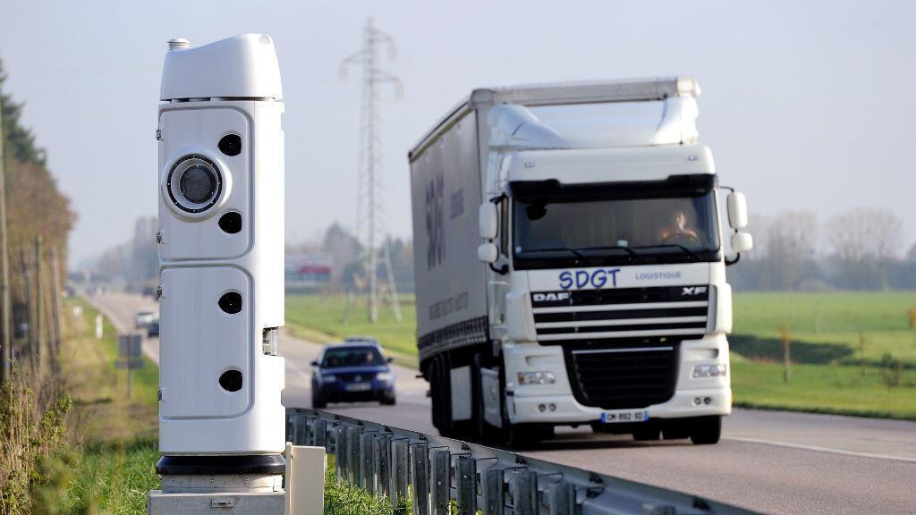 """Un camion passe devant une borne """"écotaxe"""", en novembre dernier, dans le Calvados."""