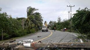 Certains poteaux électriques sont couchés sur les routes depuis le passage de Pabuk.
