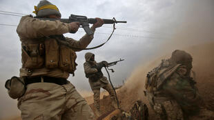 Iraqi Shiite fighters from the Hashed al-Shaabi paramilitaries fire their weapons as they advance near the town of Tal Abtah, south of Tal Afar, on November 30, 2016.