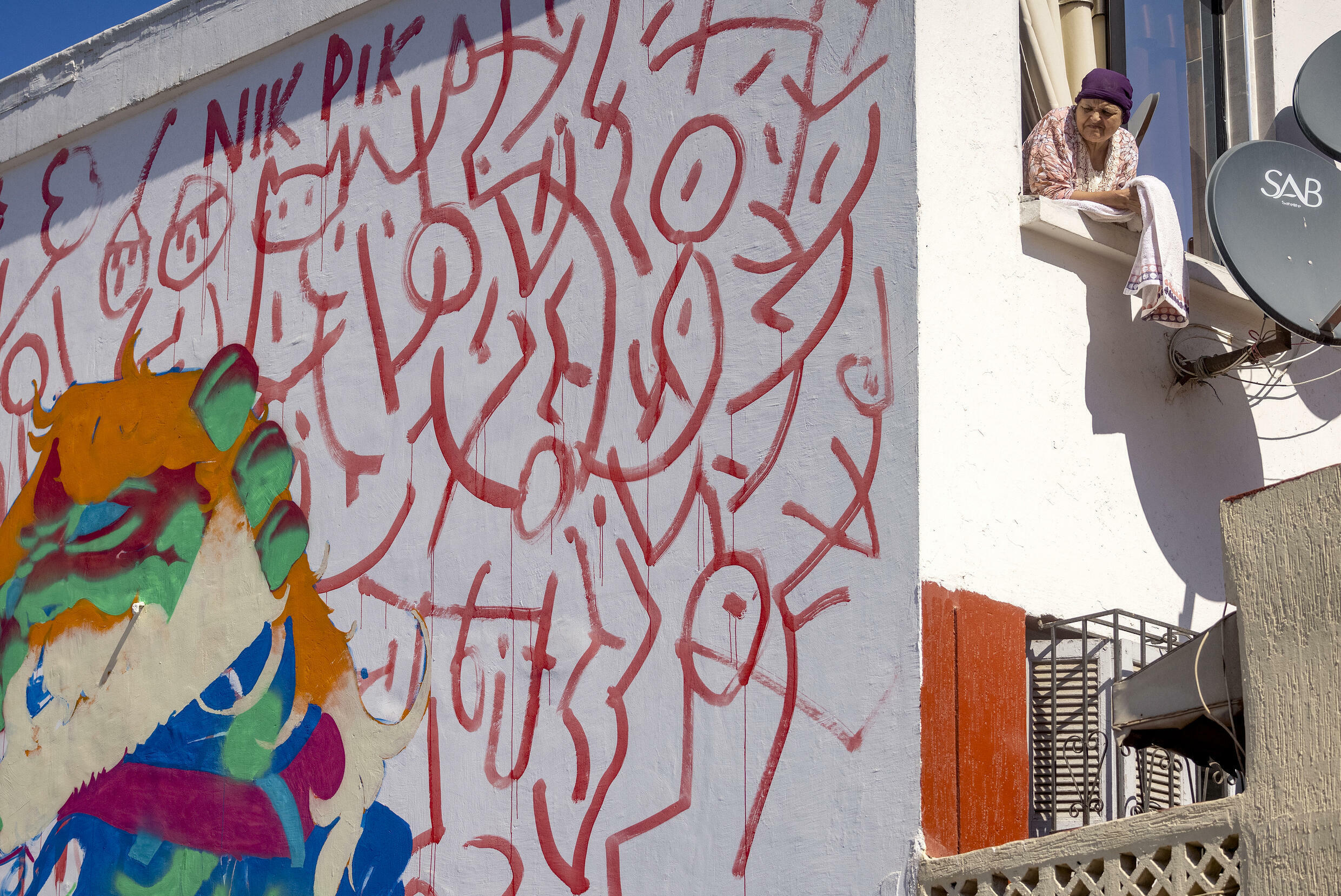 A woman looks on from her window next to a mural by Moroccan street artist Omar Lhamzi