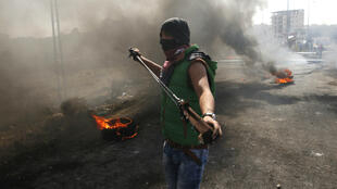 Un manifestant palestinien chargeant son lance-pierre, près de Ramallah, le 16 octobre 2015.