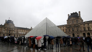 People line up outside Paris's Louvre Museum as it was closed during a staff meeting about the coronavirus outbreak on March 1, 2020.