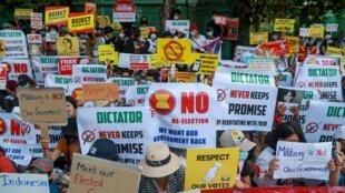 Manifestantes antigolpistas exhiben carteles cerca de la embajada de Indonesia en Rangún, Myanmar, el miércoles 24 de febrero de 2021.