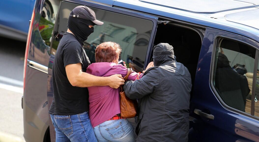 Dos hombres detienen a una mujer durante una protesta antigubernamental, en Minsk, Belarús, el 12 de septiembre de 2012.