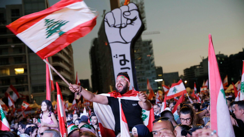 متظاهرون يحملون الأعلام اللبنانية في شوارع بيروت.