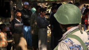 Un guardia de fronteras de Myanmar se encuentra cerca a un grupo de musulmanes rohingya frente a sus hogares en el inquietante estado de Rakhine el 25 de enero de 2019.
