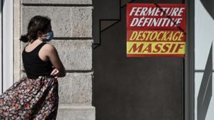 Una mujer con mascarilla pasa frente a una tienda que anuncia su cierre definitivo y la liquidación de existencias, el 5 de septiembre de 2020 en la ciudad francesa de Burdeos