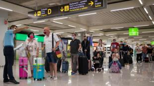Turistas llegan al aeropuerto Son Sant Joan en Palma de Mallorca el 22 de junio de 2020, ya que los ciudadanos de los Estados miembros de la UE y los de la zona Schengen ahora pueden ingresar libremente a España, sin cuarentenas de 14 días, después de un cierre nacional para detener la propagación del nuevo coronavirus.