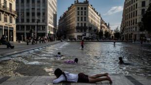 أطفال يلهون بمياه نافورة في مدينة ليون الفرنسية