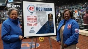 Rachel Robinson (L) and daughter Sharon flank a Jackie Robinson mural at a New York Mets game
