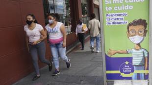 Peatones caminan con mascarillas por el centro de Ciudad de Guatemala, el 16 de julio de 2020 en medio de la pandemia de coronavirus
