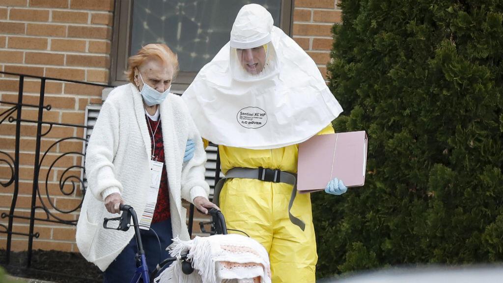 Los funcionarios médicos ayudan a un residente del hogar de ancianos de St. Joseph a abordar un autobús, luego de que varios residentes dieron positivo por enfermedad por coronavirus Covid-19 en Woodbridge, Nueva Jersey, EE. UU., el 25 de marzo de 2020.