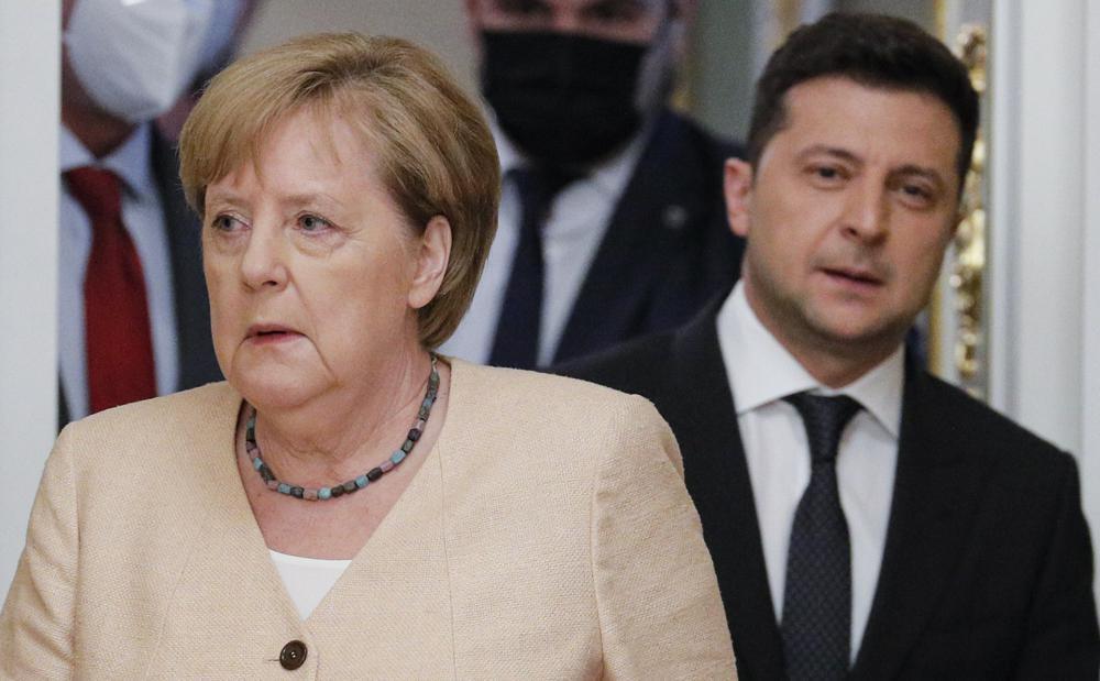El presidente ucraniano Volodymyr Zelenskyy, a la derecha, y la canciller alemana Angela Merkel entran en una sala para una conferencia de prensa conjunta después de sus conversaciones en el palacio Mariinsky en Kyiv, Ucrania, el domingo 22 de agosto de 2021. La canciller alemana Angela Merkel llegó a Kiev para una visita de trabajo para reunirse con altos funcionarios ucranianos.