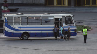 Three hostages walk out of a seized passenger bus in the city of Lutsk, Ukraine, on July 21, 2020.